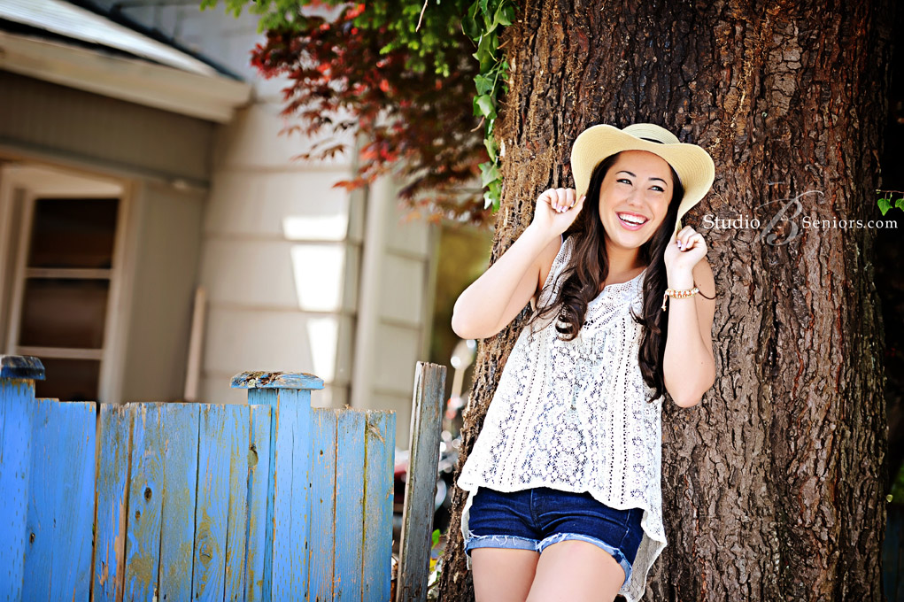 Pretty-teenager-in-jean-short-and-big-floppy-hat-laughing-by-a-tree