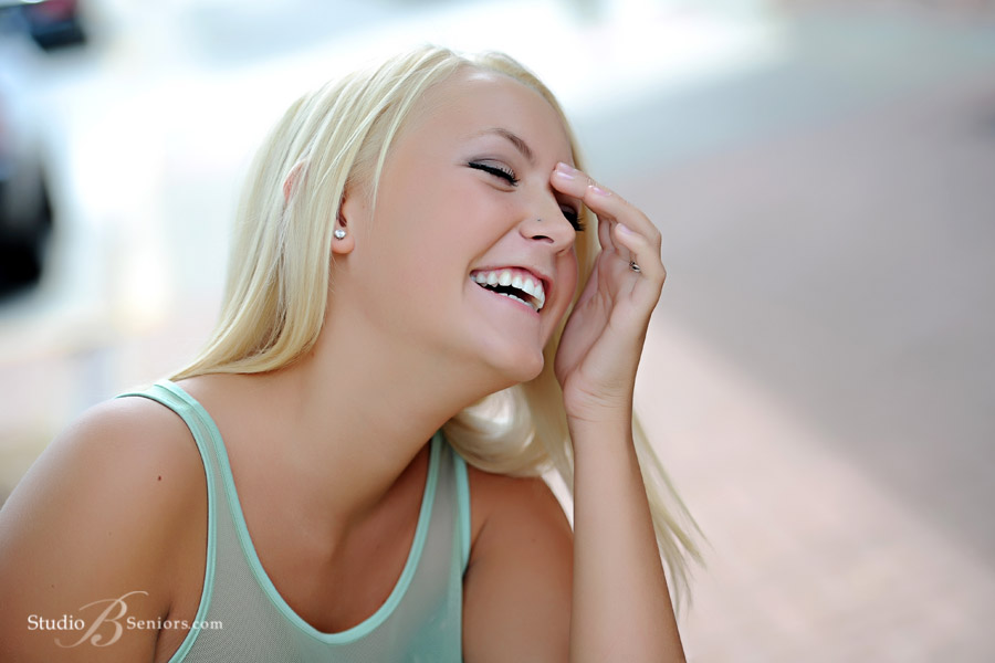 Pretty-blonde-teen-laughing-during-senior-pictures at Studio B Portraits