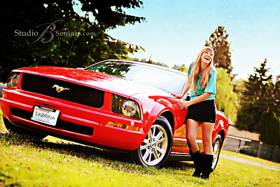 Senior-pictures-in-Issaquah-of-pretty-blond-Mount-Si-2012-girl-with-red-mustang-in-field-laughing2