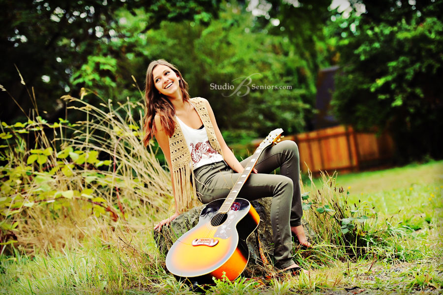 High-School-Senior-Pictures-of-pretty-girl-outdoors-in-Issaquah-laughing-with-guitar