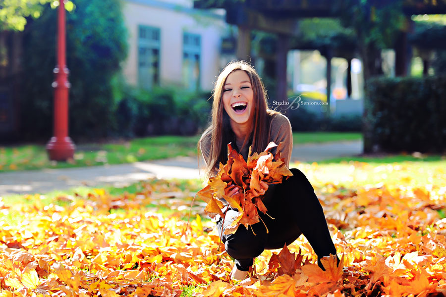 High-school-senior-girl-laughing-in-the-fall-leaves-in-Issaquah-near-Bellevue
