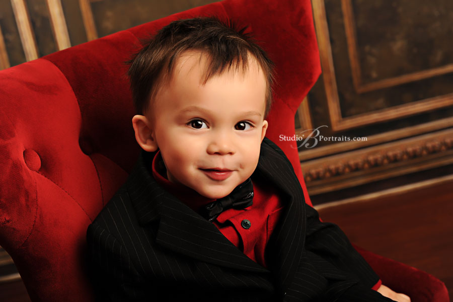 Holiday-portrait-of-little-boy-in-red-velvet-chair-at-Studio-B-Portraits
