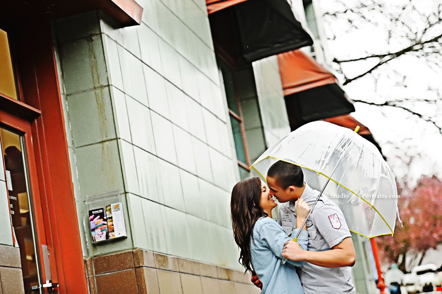 Cute-couple-kissing-in-the-rain-under-an-umbrella-in-Seattle