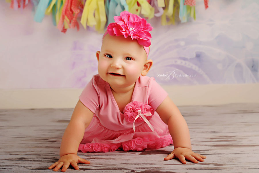9-month-baby-girl-in-pink-dress-with-flower-at-Studio-B-Portraits-in-Issaquah