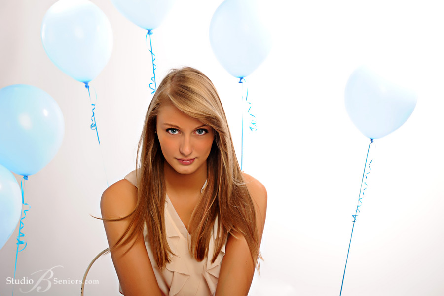 Blonde-high-school-senior-girl-with-balloons-and-orange-dress-at-Studio-B-Portraits