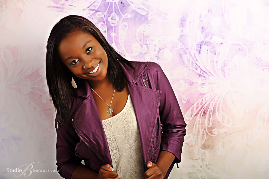 High-School-Senior-pictures-of-black-teenage-girl-smiling-in-purple-leather-coat-at-Studio B