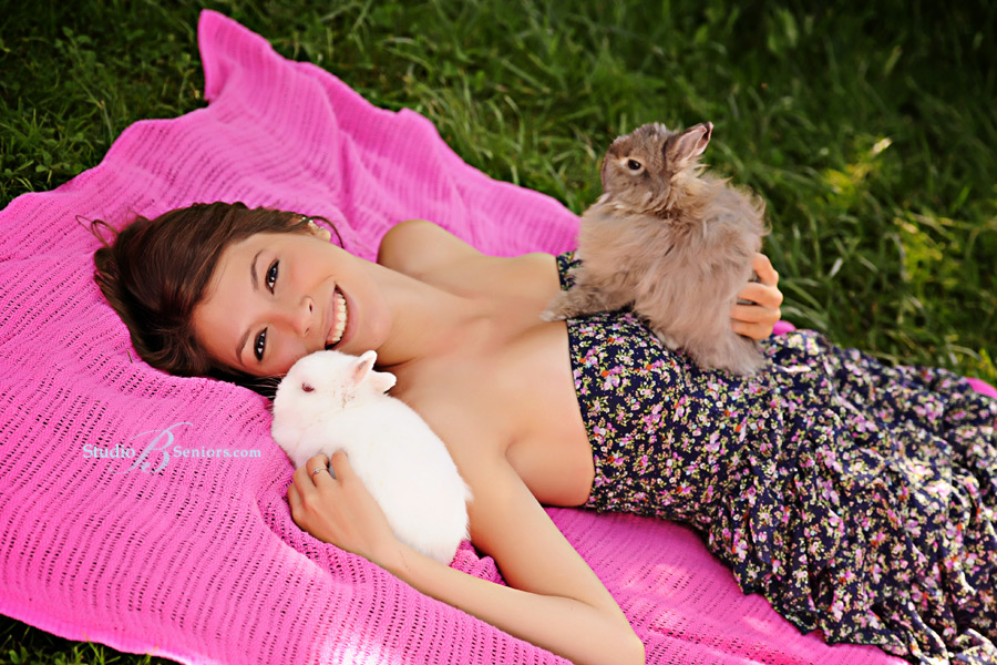 High-School-senior-pictures-of-girl-with-two-bunnies-on-a-pink-blanket