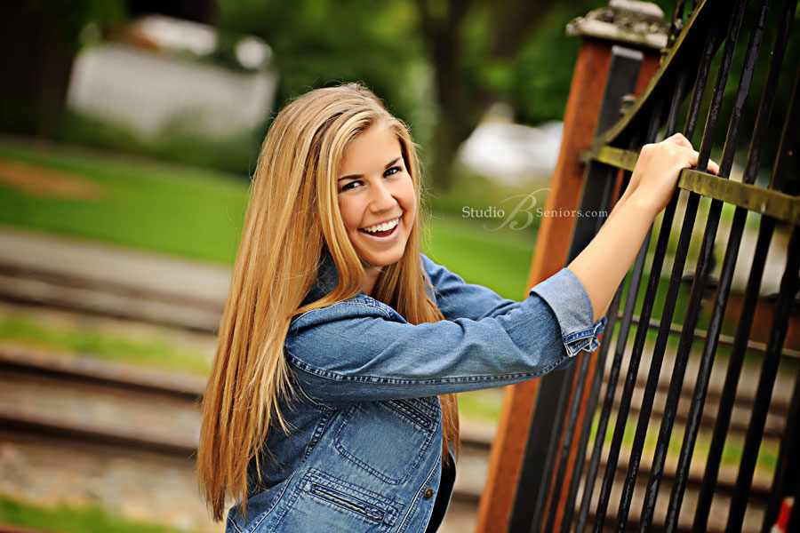 Senior-pictures-of-pretty-girl-laughing-at-gate-by-Studio-B-Portraits