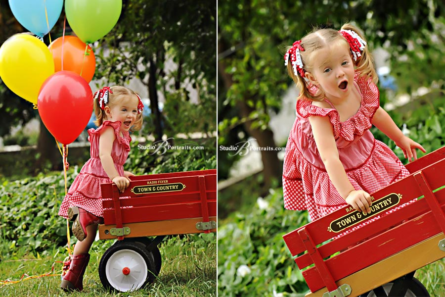Childrens-portrait-of-2-year-old-girl-laughing-in-radio-flyer-wagon-with-balloons