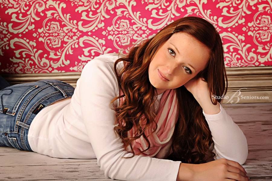 Interlake-High-School-Senior-Pictures-of-red-head-girl-against-pink-damask-background-at-Stuido-B