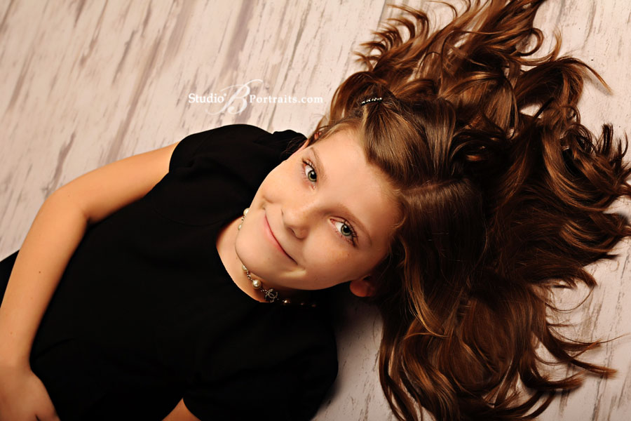 Pretty-little-girl-in-black-dress-during-family-portraits-at-Studio-B-in-Issaquah