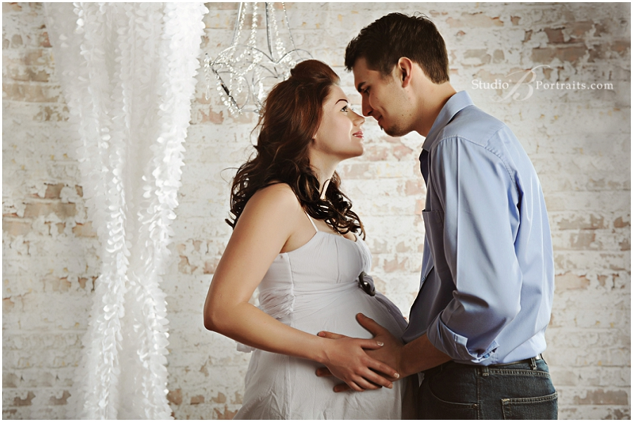 Maternity portraits with pretty couple in front of brick wall and chandelier at Studio B Portraits