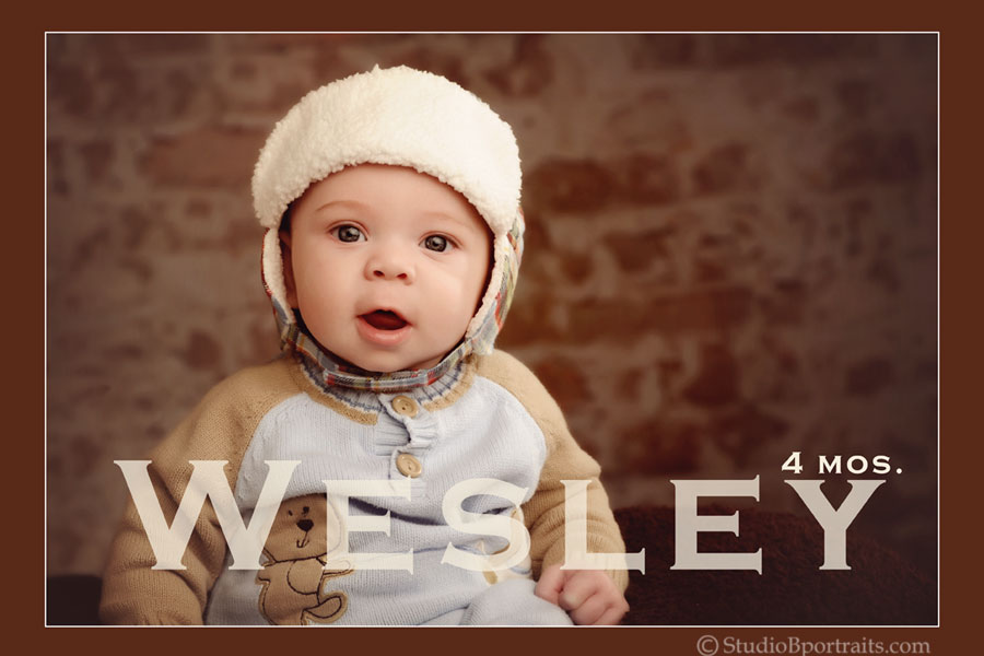Cute-baby-boy-in-hat-against-brick-wall-4-months-at-Studio-B-Portraits