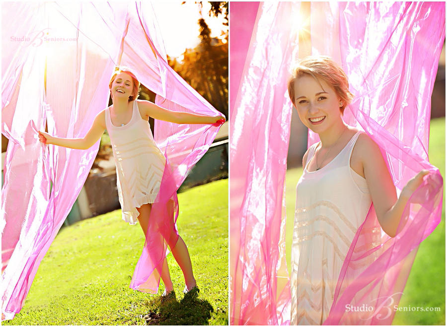 Best Senior Pictures_Studio B Portraits_Girl with pink fabric laughing outdoors in white dress