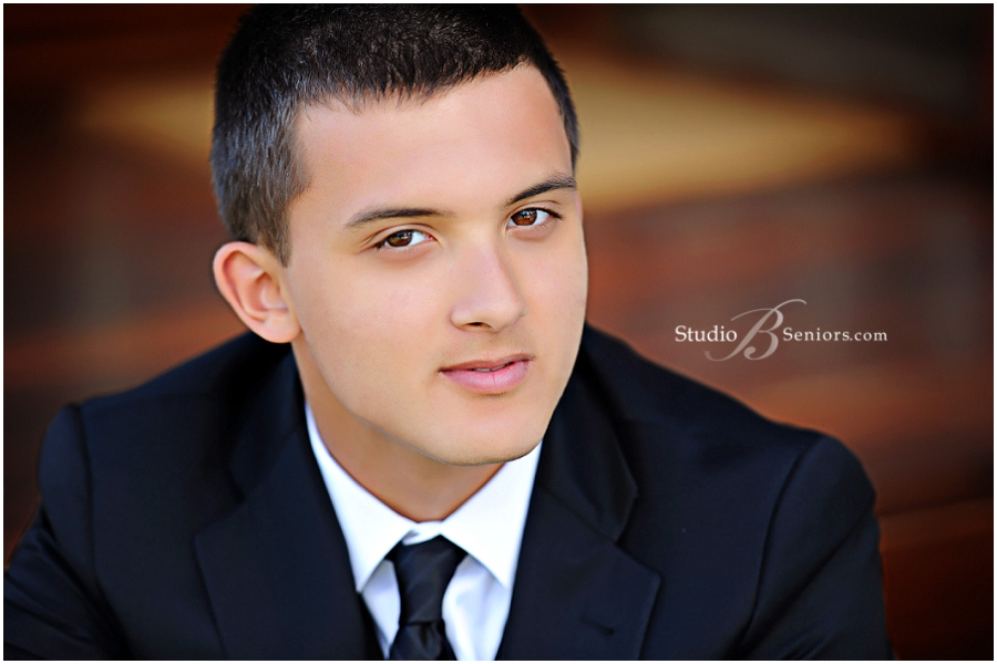 Senior guy in black suit and tie outdoors during senior pictures_Studio B_0019.jpg