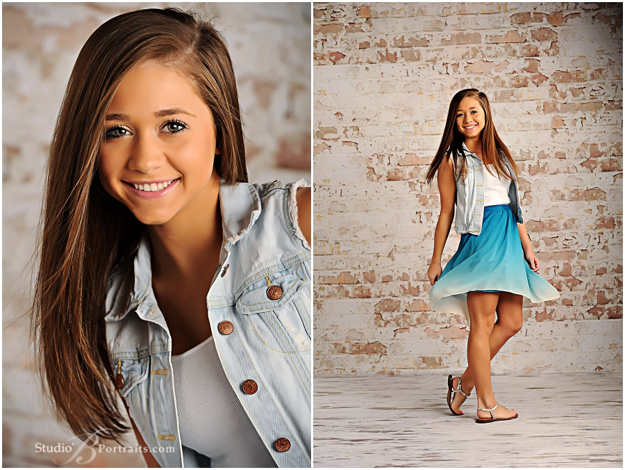 Senior pictures of girl spinning in blue dress next to brick wall_Studio B_0023.jpg