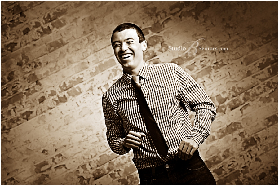 Senior guy laughing in tie and button down shirt at Studio B Portraits