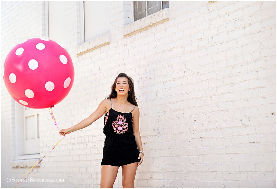 Senior girl in black romper holding hot pink balloon _Studio B Portraits_0124.jpg