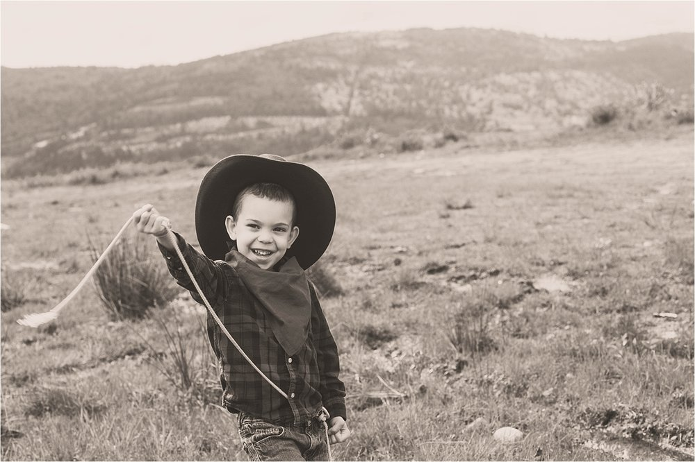 4 year old dressed as cowboy swinging rope in a field