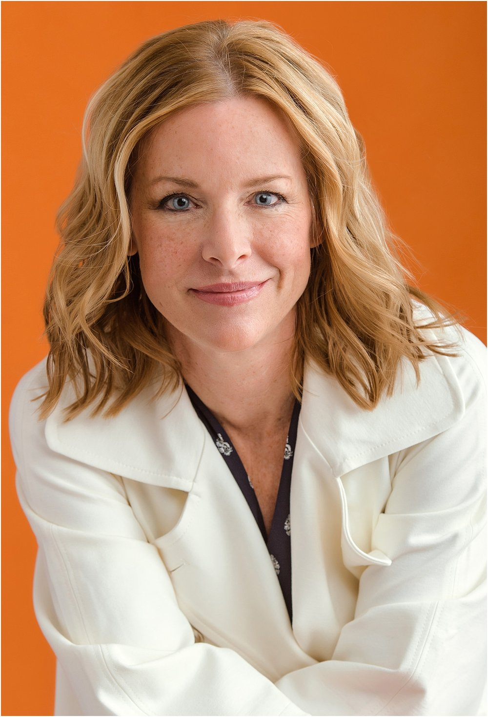 Female Consultant photographed on orange background in cream coat.jpg