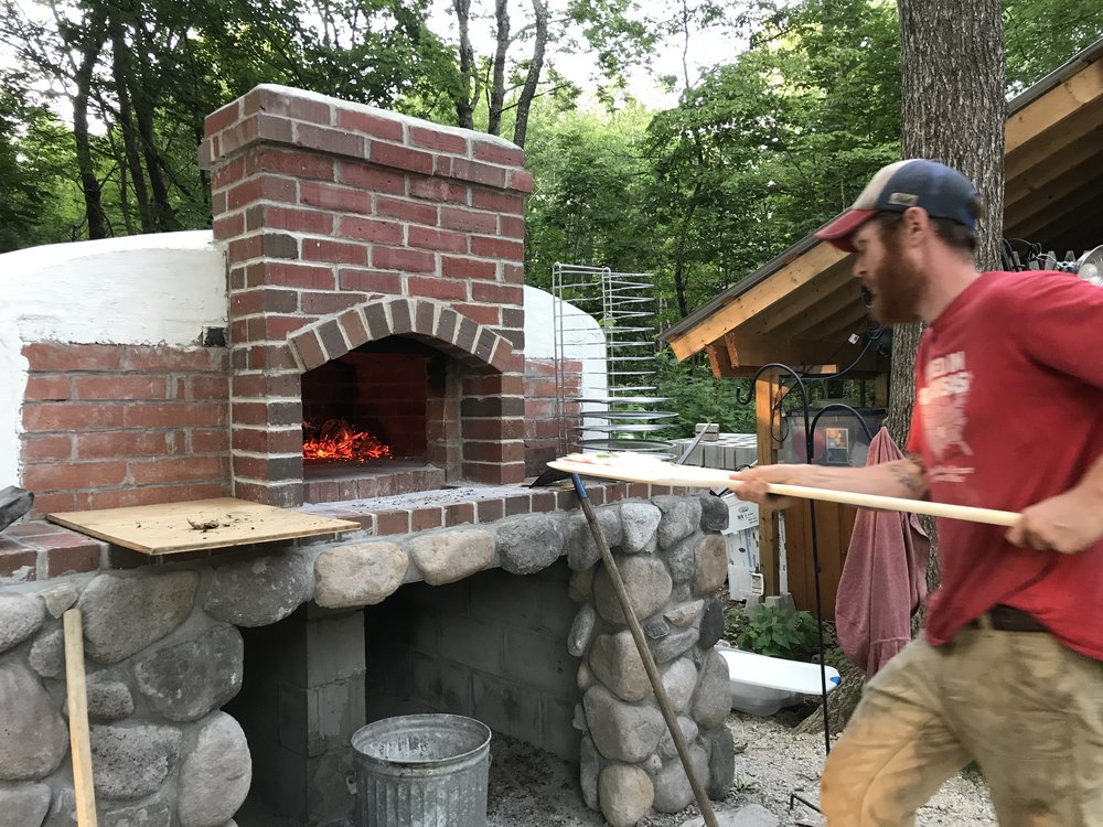Farmer Brian being the pizza oven master!