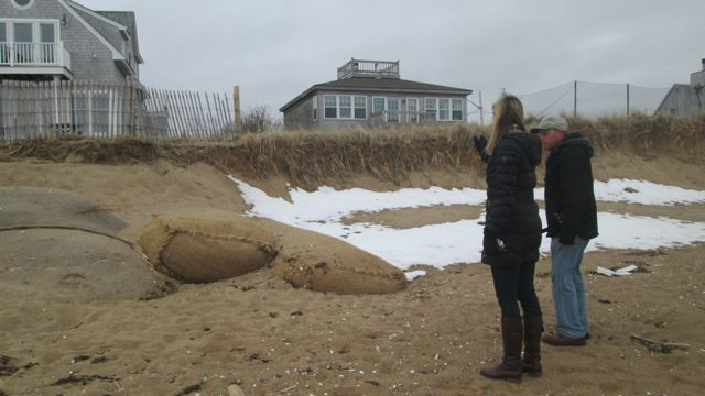 Safe Harbor Director Gordon Peabody, shown here with Newburryport Conservation Agent Julia Gotfreidson, inspect ongoing coastal beach and dune erosion.  Shown here, Geo-tubes, are one of the techniques the municipality was already working with is considered a semi-soft solution because it incorporates sand to absorb energy instead of stone, which would re-direct the energy.