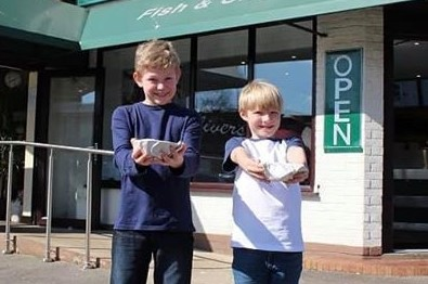 Ollie Webb (L) and Edward Walton (R) practice asking for more chips at Oliver's Chip Shop in Old Basing