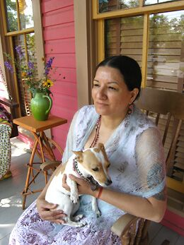 Sandra Cisneros sitting on the front porch of her home in San Antonio, Texas.