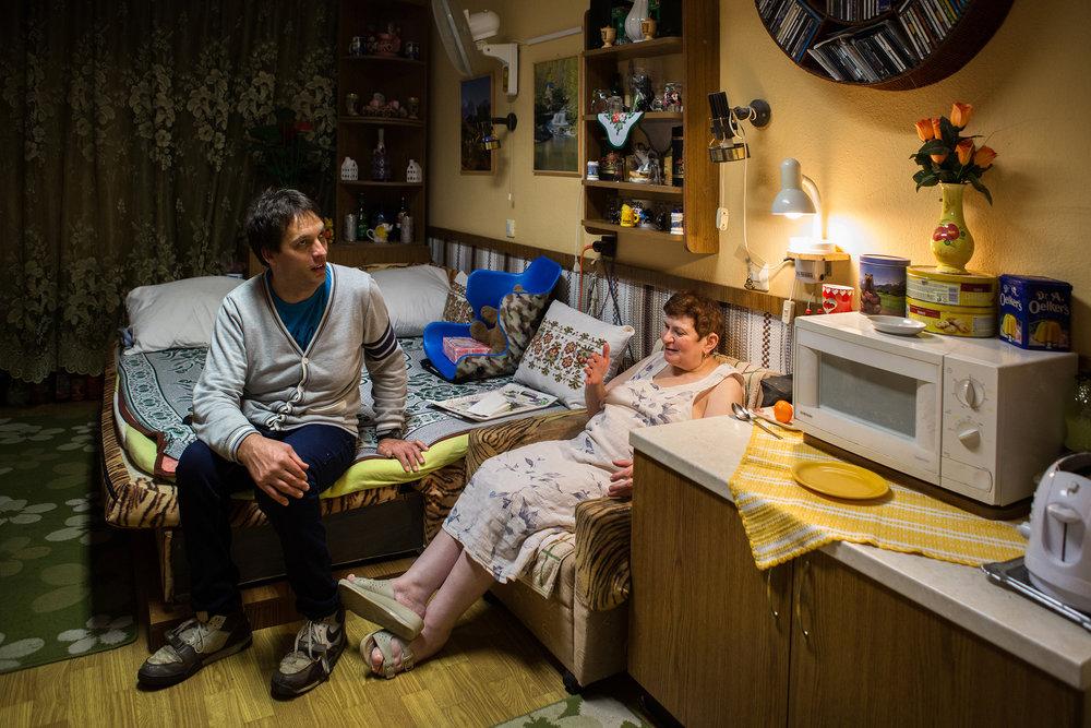 """Szociális otthonban lakik, szobáját kedvesével, """"Sziporkával"""" osztja meg. A gondosan berendezett nappali otthonosan hat, de a konyhán, étkezőn, fürdőn osztozniuk kell az emelet többi lakójával. A napi háromszori étkezés, orvosi felügyelet biztosítva van számukra, de ha az ellátásból és Laci keresetéből kijönne, a pár szívesebben lakna önállóan, albérletben. Az otthonban nincs sok szabadidős lehetőség, és mivel zömmel inkább idősek lakják, a társaság sem feltétlen nekik való."""