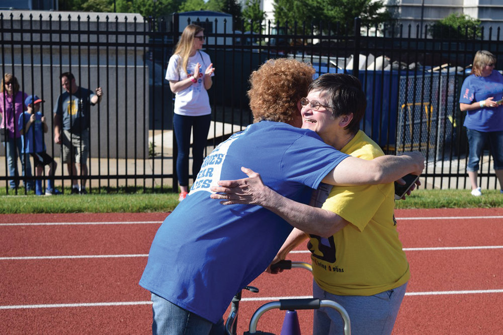 A congratulatory hug after crossing the finish line at the State Summer Games at Missouri State University in Springfield