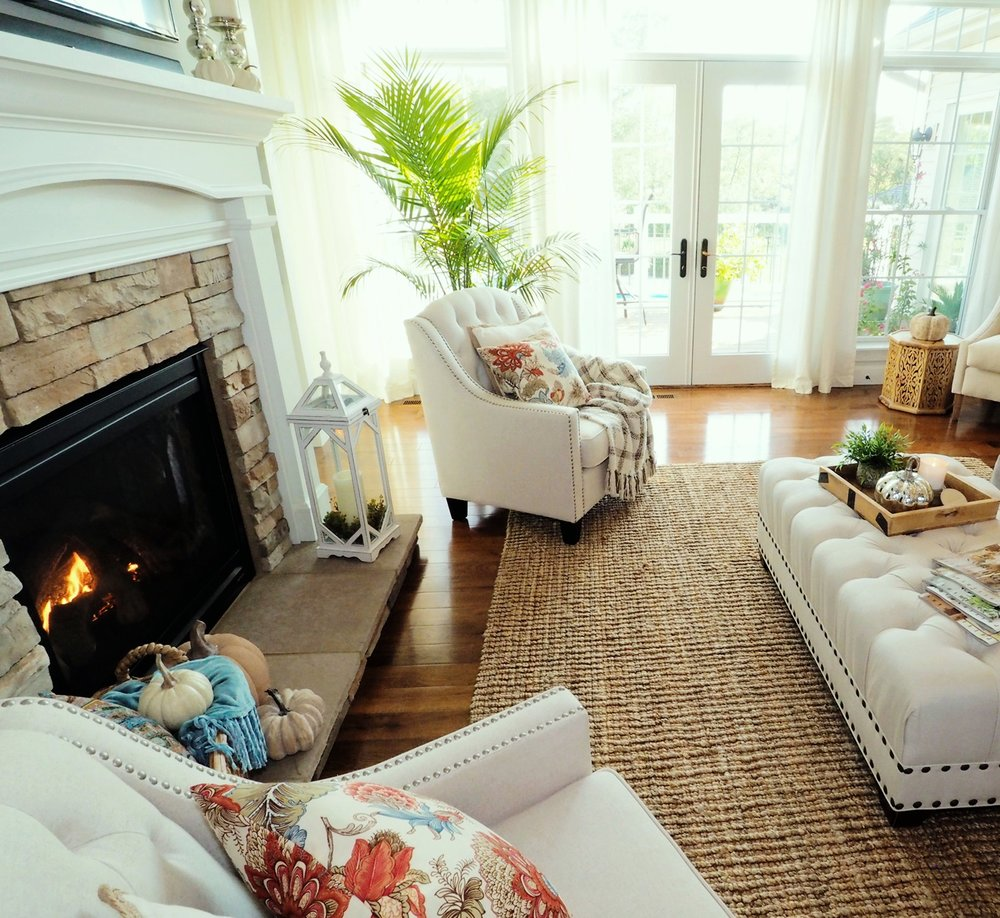We've been chilly enough to have the fireplace on and I am loving it! If I can't be outside warmed by the sun, the next best thing is to be inside and sitting cozy right here in front of this fire! So here are those beautiful pillows up close. I've had them for so long I don't even remember where they came from. In fact, I remember purchasing them for fall decor when we had our first Thanksgiving in this house and that was about 7 years ago! See, time really does fly! We moved in December of 2009 and our first Thanksgiving was November of 2010! Wow! That was a fast 8 years for sure! --  Similar Jute Rug  HERE . Similar tufted ottoman sold  HERE .
