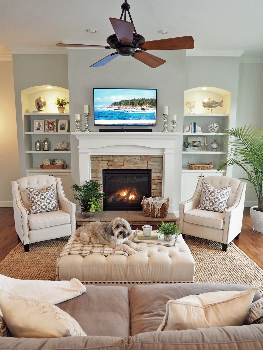 This photo is the perfect example of the seasonal changes! I took this on a gray winter's day with clouds and a light dusting of snow on the ground. Look how different the Conservative Gray appears on the fireplace and shelving walls. It is a deeper gray/blue/green as compared to the daytime summer photo.