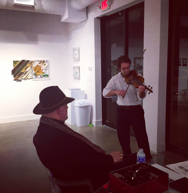 The artist Nall's opening reception February 11, 2016 at Octavia Art Institute Houston. The artist Nall listening to Matthew Madonia play the violin for guests.