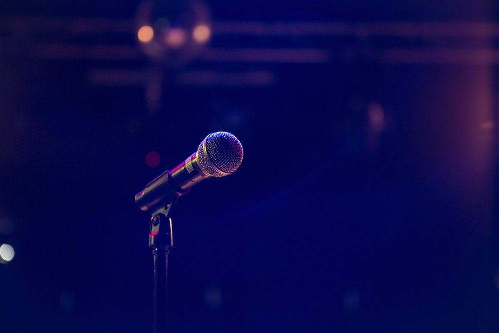 Dynamic microphones  are what you'll see on stages and live sound environments like concerts and stand-up.