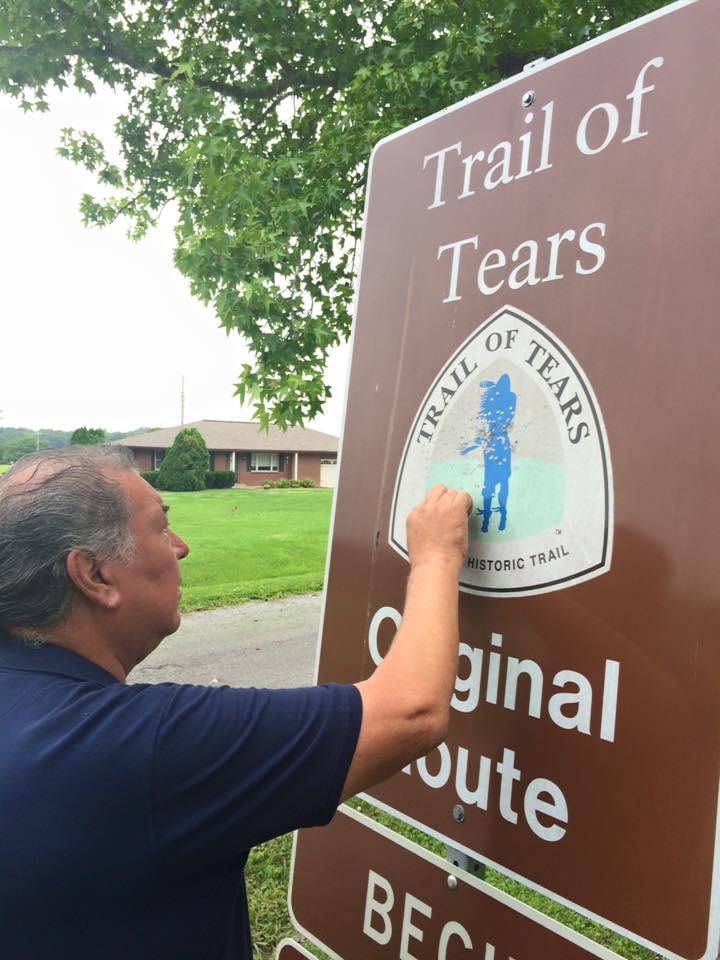 Thomas Studie examines a Trail of Tears Historical sign that has been shot by buckshot