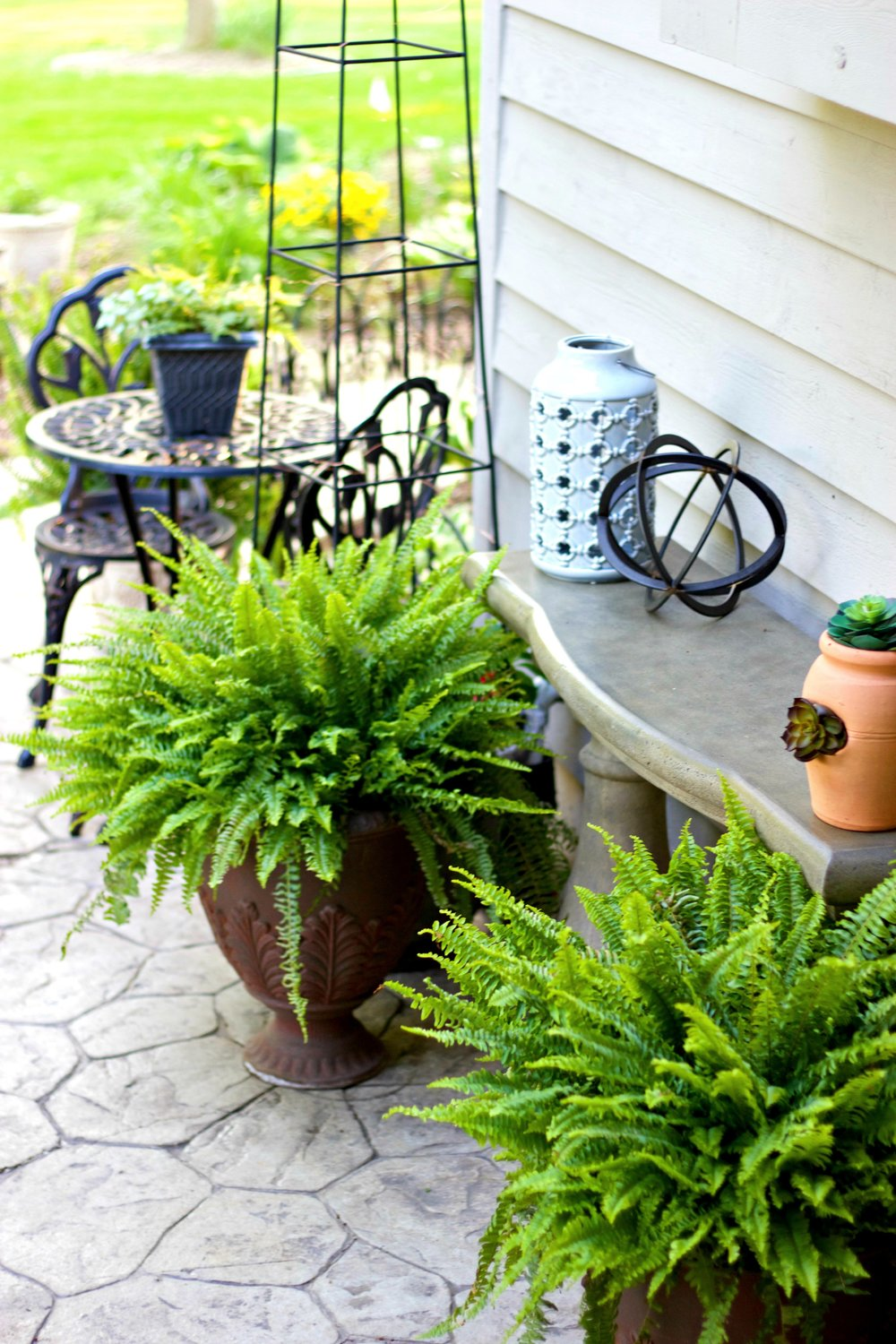 I just got this table and didn't love it until I added the ferns, which tied it in nicely with the rest of the patio.    (The table is from Grandin Road - click here to see it)