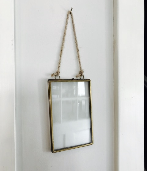 - FIND AN INTERESTING FRAMEI love these see through frames! They are very industrial and charming, in my opinion. You can open up the frame and sandwich and image in the frame. With this frame, I haven't put an image in it as I feel the frame itself is an interesting piece. It also adds a reflective surface to the wall as you can see by the back doors image in the glass.