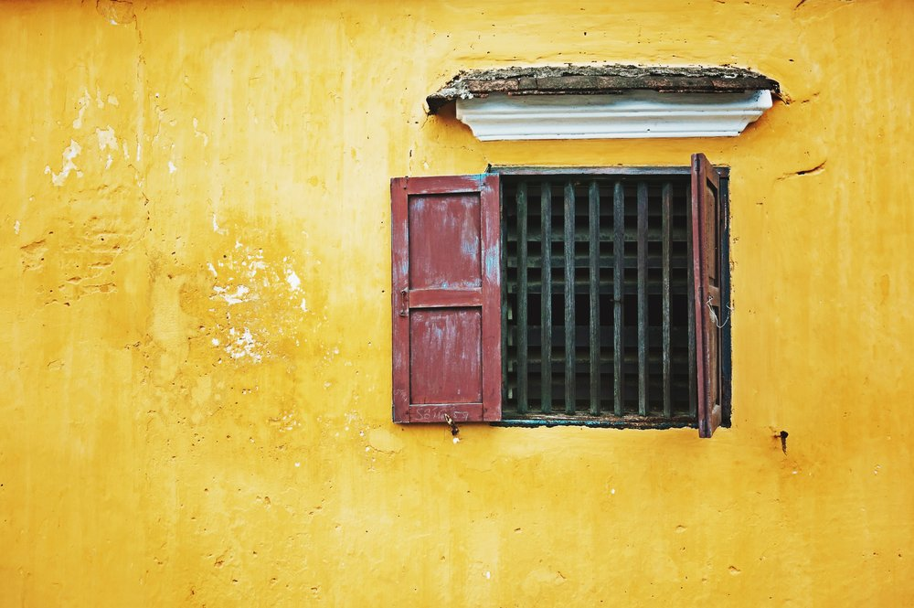 yellow wall with red brown window