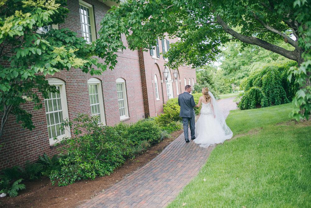 NH Wedding Photographer: newlyweds walking at Saint Anselm