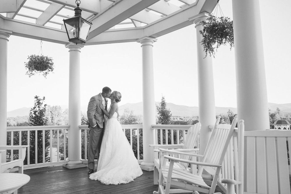 NH Wedding Photographer: bride and groom kissing on front porch