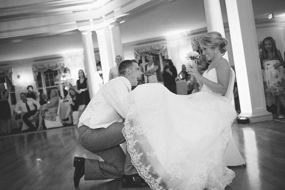 NH Wedding Photographer: groom takes garter from bride