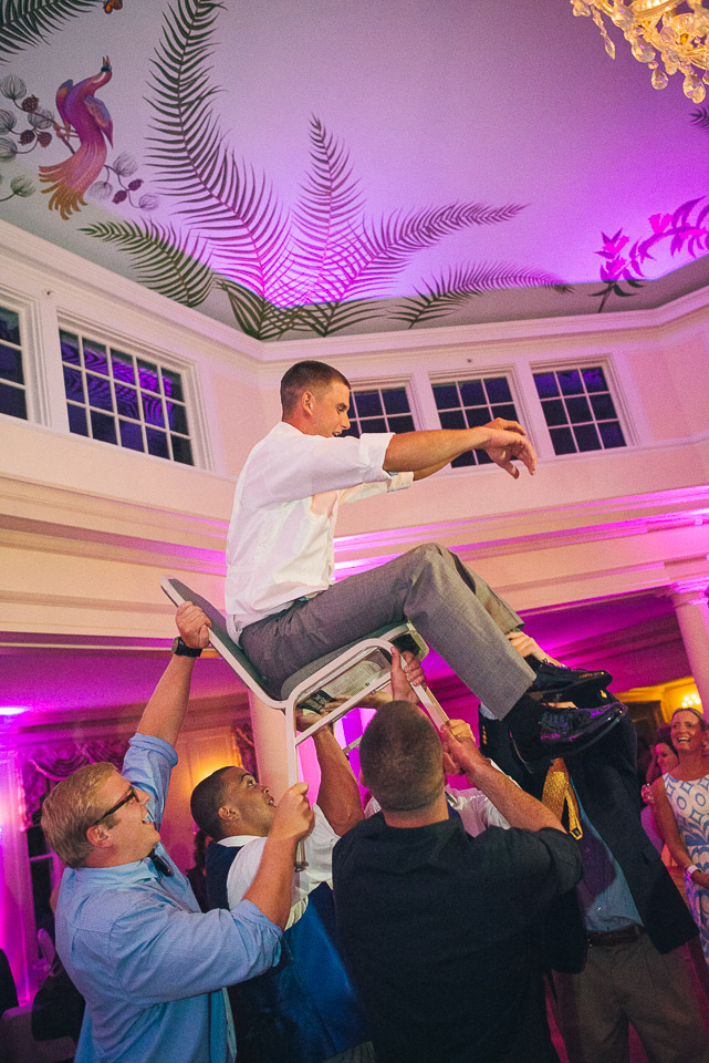 NH Wedding Photographer: wedding reception groom lifted in chair