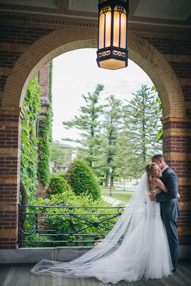 NH Wedding Photography: newlyweds on porch at Saint Anselm