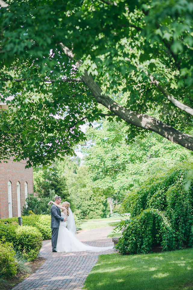 NH Wedding Photography: couple on tree covered walkway