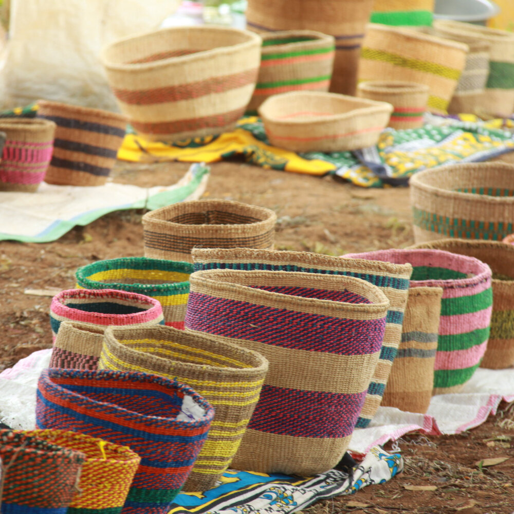 ABOUT THE BASKETS   These unique baskets are made out of sisal which is grown either on farms belonging to the basket weavers, or else purchased from sisal estates in coast province. The leaves of the sisal plant are used to obtain a fibre which is rolled to twine, and then be woven to a basket.  The Taita ladies from the Kasigau Weaver's Group dye the fibres themselves and then roll the twine on their lap. Making baskets is a very labour intensive art. The baskets come in a number of different colours and patterns, with each design entirely made up by these artistic Taita ladies!