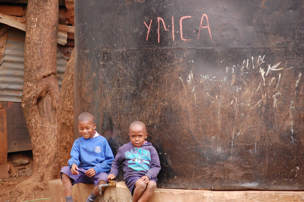 Sharing a drink of water at the YMCA in Kibera