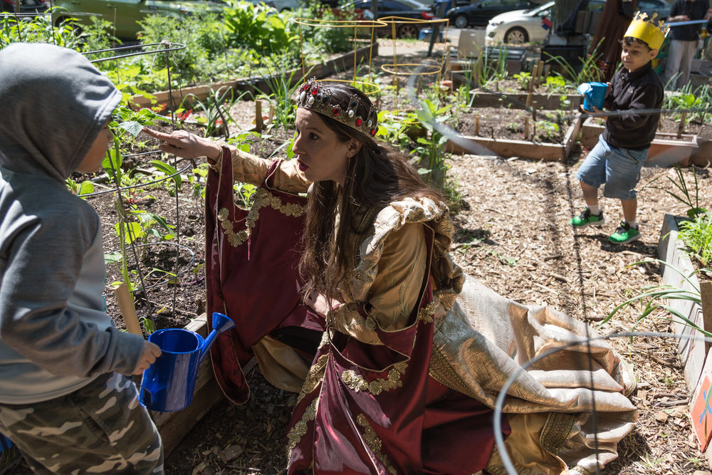 Queen Maria Isabella (Allyssa O'Donnell) helps preschoolers water the garden at the Altgeld Sawyer Corner Farm.