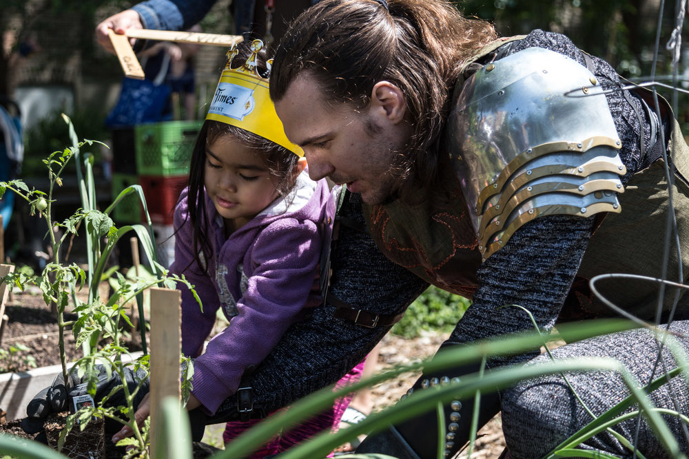 Michael Kiburz, the Green Knight, helps a preschooler plant tomatoes at the Altgeld Sawyer Corner Farm.