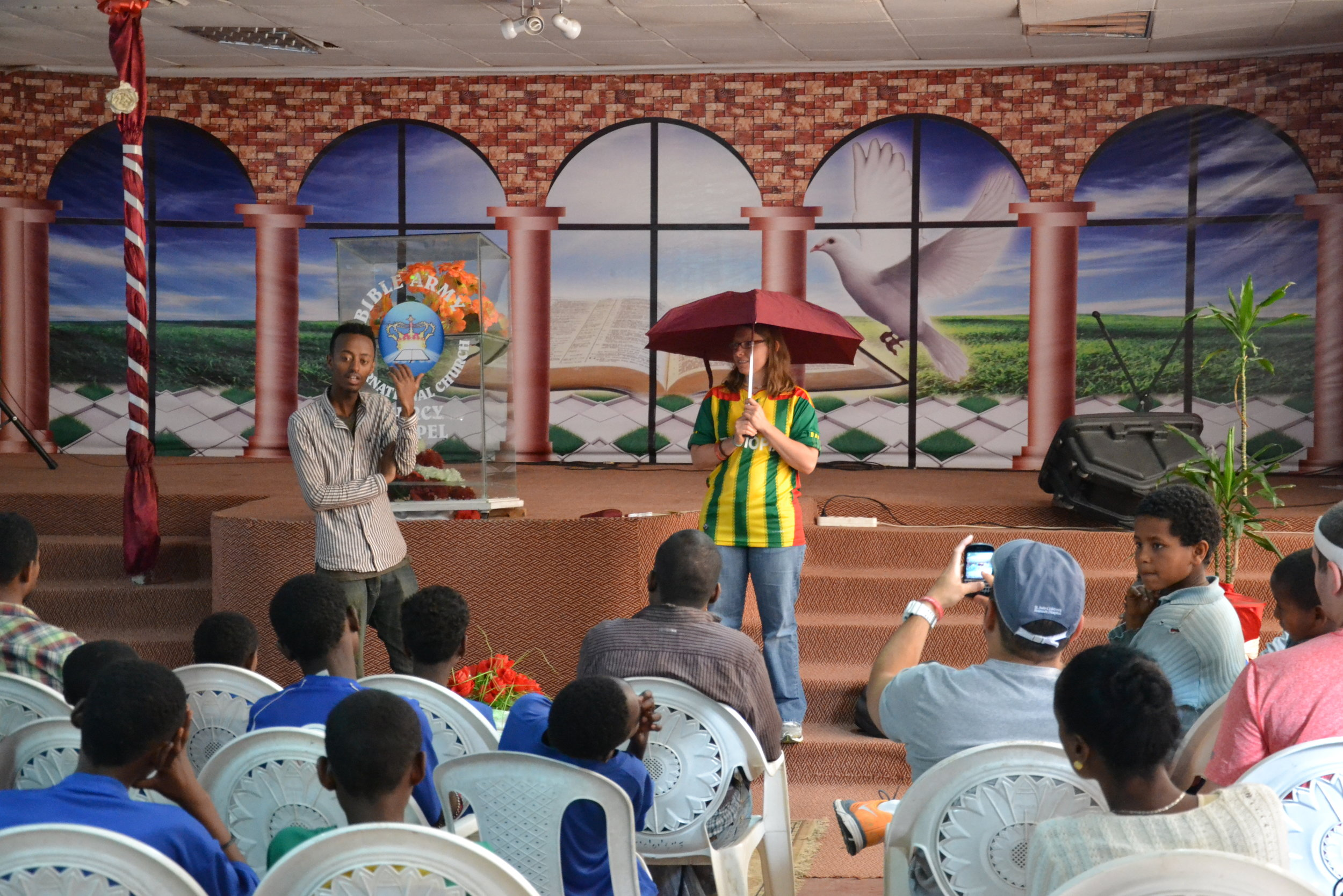 Cathy using an umbrella to demonstrate the enveloping presence of God.