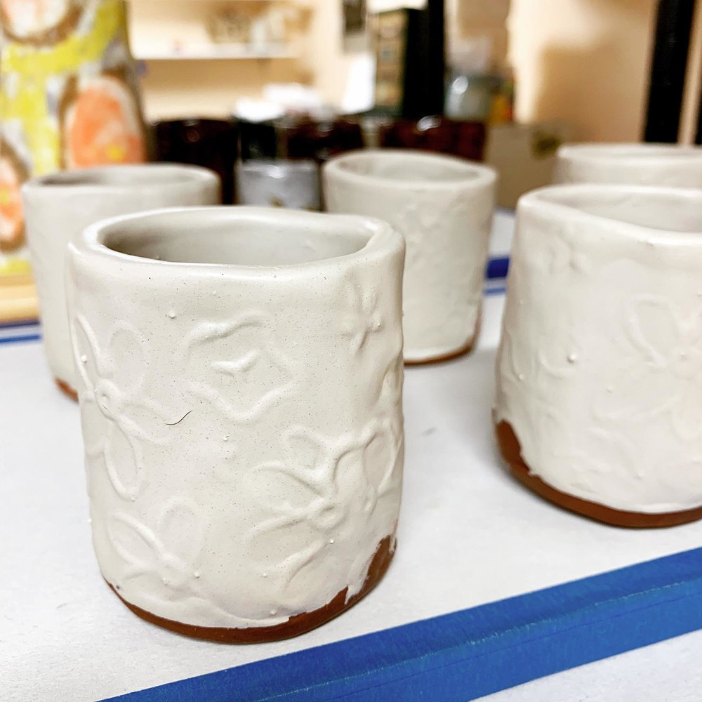 Floral Whiskey Cups -  Hand stamped whiskey cups with a layer of white slip, awaiting the bisque kiln.